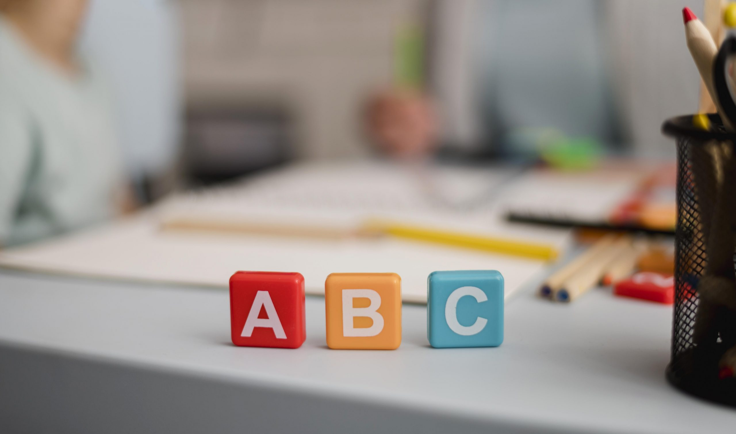 front-view-of-letters-on-cubes-with-defocused-tutoring-session-in-the-back
