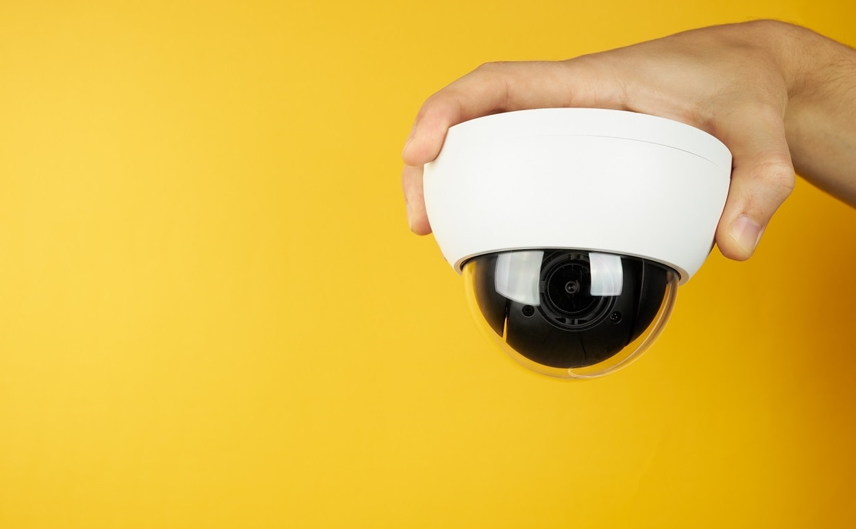 The wait cctv surveillance camera at palm on a yellow background with copy space. security and privacy concept.